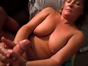 Mature wife using both her hands to stroke the boner squeezing it hard